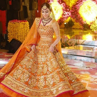 Indian designer lehengas | Orange | Twirling bride | A