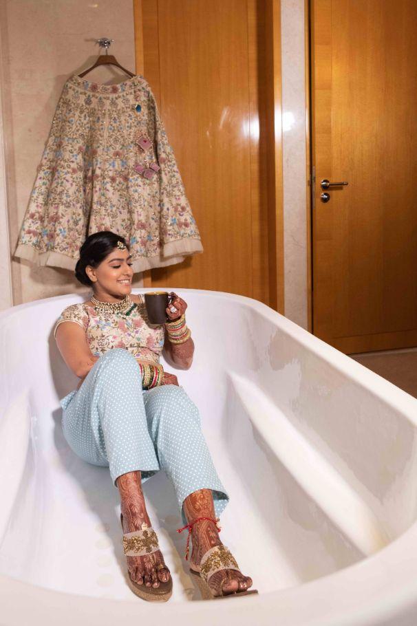 getting rerady , indian bride in bathtub , indian bridal lehenga , indian wedding cake ,  pastel wedding, grand wedding cake Chandelier cake, wittyvows , wedding blog , indian couple