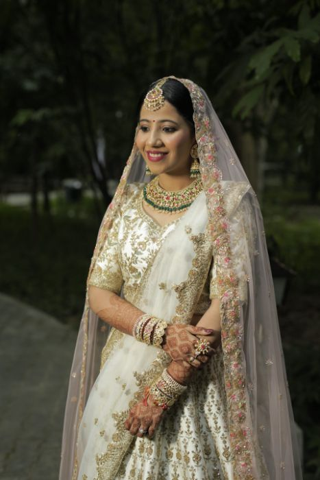 beautiful bride in ivory and gold lehenga   Intimate Wedding in Jim Corbett