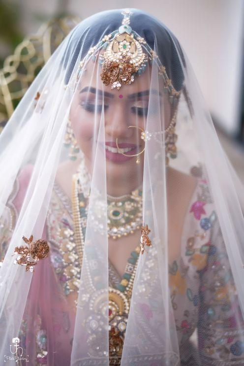 beautuful bride in pastel pink lehenga | bridal veil shots | Beach Wedding in Alibaugh