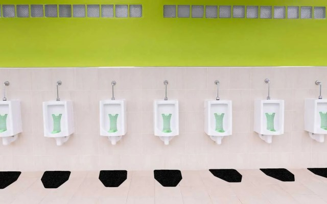 Cucumber Melon Splash Hog Vertical Urinal Screens With Black Original Cut Antimicrobial Urinal Mats From WizKid Products Installed In A Public Restroom
