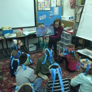 Kiwanis member reads to Norge students.