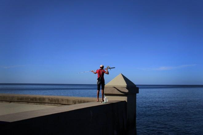 A fisherman stands on the Malecon, a seawall along the coast of Havana, Cuba.