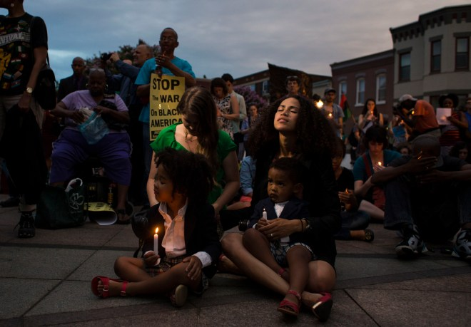 Maybelline McCoy, 30, of Washington, DC, sits in silence holding candles with her children Micah McCoy, 4, and Malakai McCoy, 2, as people gather in front of the African-American Civil War Memorial on U Street in Washington, DC, during a prayer vigil in remembrance of the victims killed in the shooting at the historic Emanuel AME Church in Charleston, SC, on Friday, June 19, 2015. The vigil was hosted jointly by the NAACP DC Branch and National Black United Front and over 300 individuals were in attendance.
