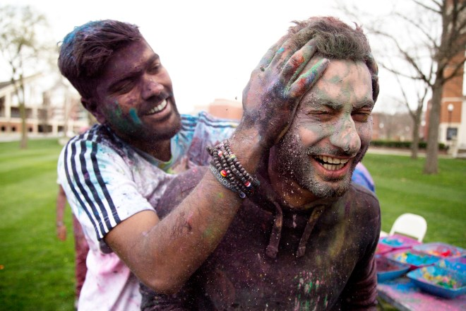 Chirag Ar, a sophomore from India, sneak attacks Saudi Arabian student, Mustafa Almarhun with handfuls of brightly colored holi powder during the 2016 Holi Festival hosted by the Indian Student Association on South Lawn at Western Kentucky University on March 19, 2016. Holi is a Hindu celebration of good over evil that is traditionally celebrated in India and southeast Asia. || Photo by Alyse Young