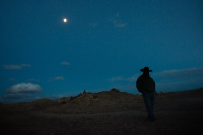 Larry Gordy walks among the testing pits and waste mounds on his grazing lands on the Navajo Nation near Cameron, Arizona. He remembers trail riding with his father, a Navajo uranium miner across this poisoned land before his death.
