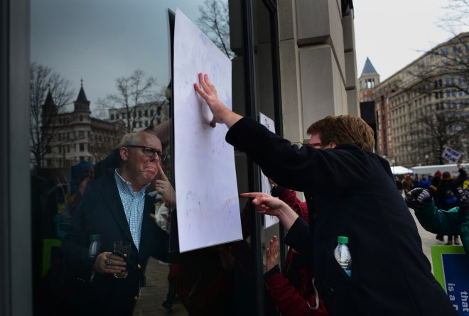 "A protestor points to the word ""Fascist"" on his sign while a Trump supporter fakes tears in response from inside a restaurant on Pennsylvania Avenue. Demonstrators shouted and pressed signs against this window while those inside sipped champagne and watched. This continued until a woman got up and closed the blinds."