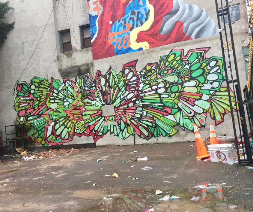 Mural of a burst of green seed shapes and red highlights at the base of a larger mural in a rare abandoned lot in Manhattan