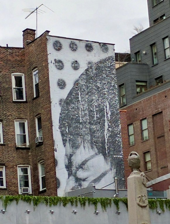 4 story mural of a face Squinting while circles fall in the background