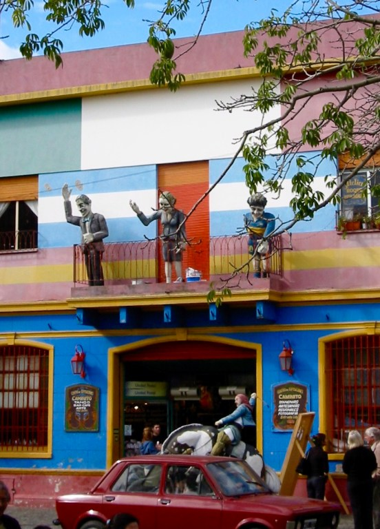 Statues of Carlos Gardel, Evita, Maradona on a Balcony overlooking Caballito with a Cabellero riding hard below.