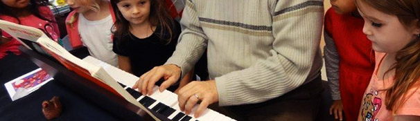 Guest lecturer plays piano for the children