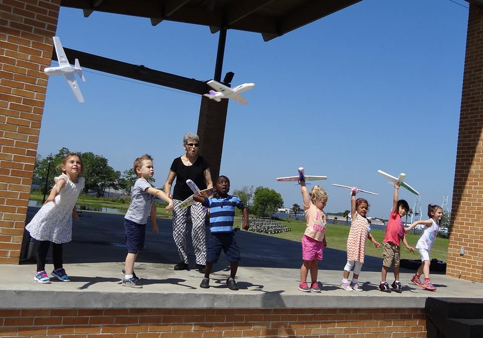 Children fly paper airplanes with teachers