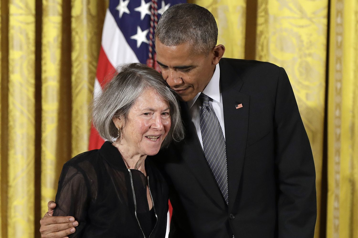 President Barack Obama embraces poet Louise Gluck before awarding her the 2015 National Humanities Medal during a ceremony in the East Room of the White House, Thursday, Sept. 22, 2016, in Washington. (AP Photo/Carolyn Kaster)