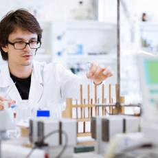 young, male researcher/chemistry student carrying out scientific research in a lab (shallow DOF; color toned image)