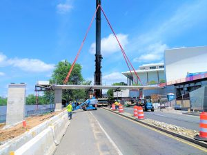A pedestrian bridge being picked by a large crane