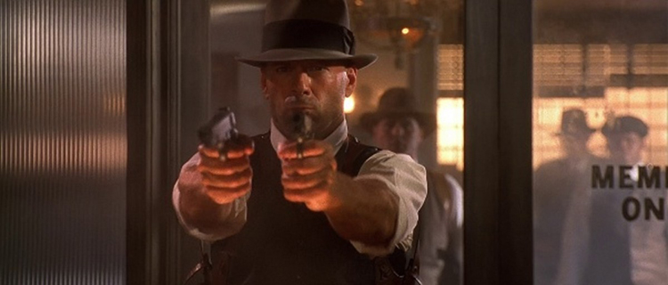 Bruce Willis, as John Smith, is Never without Two Guns in Last Man Standing