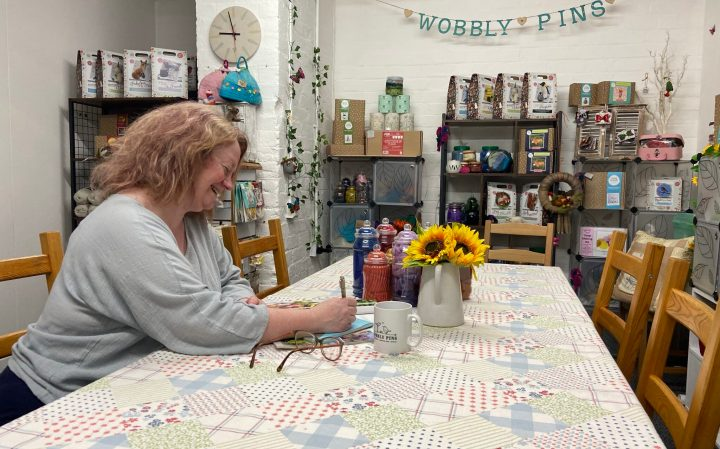 Photo of Jacqueline, owner of Wobbly Pins Craft Classes and Gift Shop, at work in her studio.