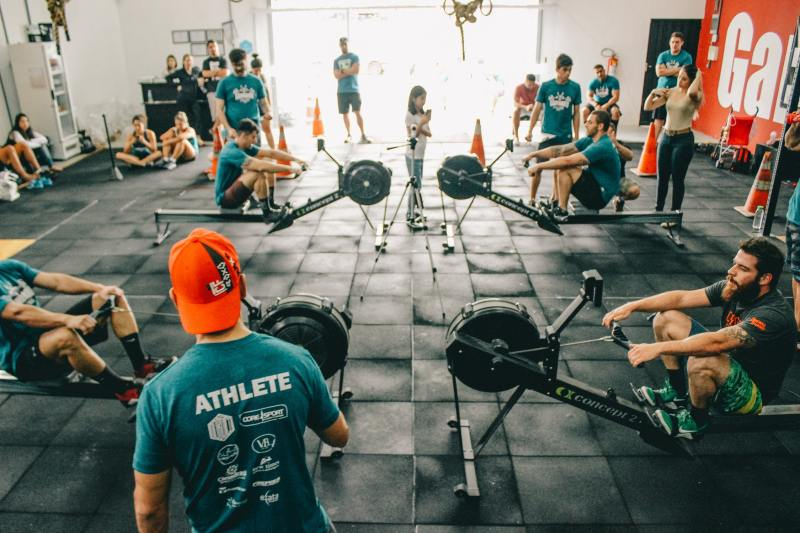 A gym of CrossFit athletes rowing.