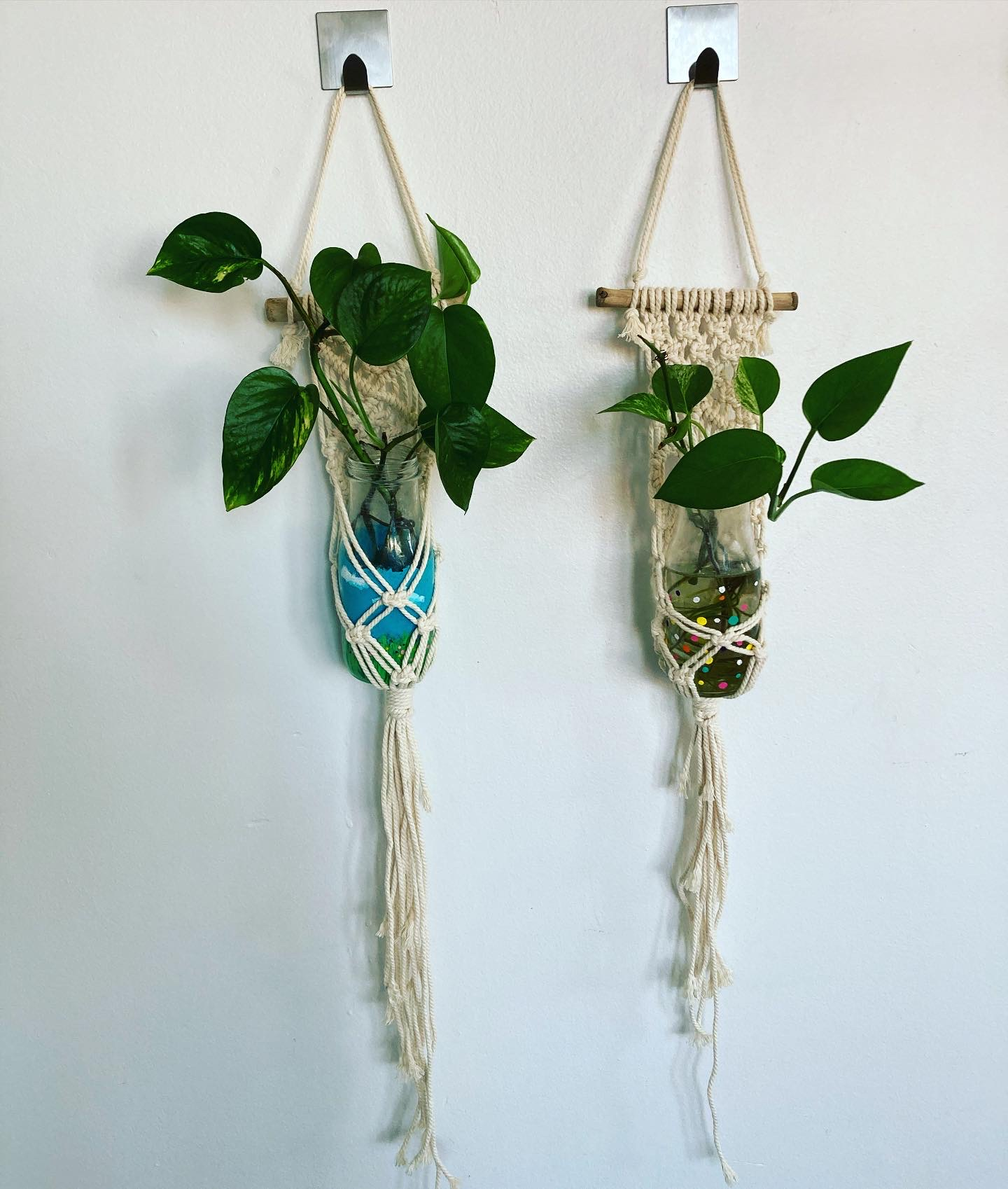 two small beige macrame hangars, each holds a small bottle filled with watter and a plant cutting. The bottle on the left is painted with a custom design