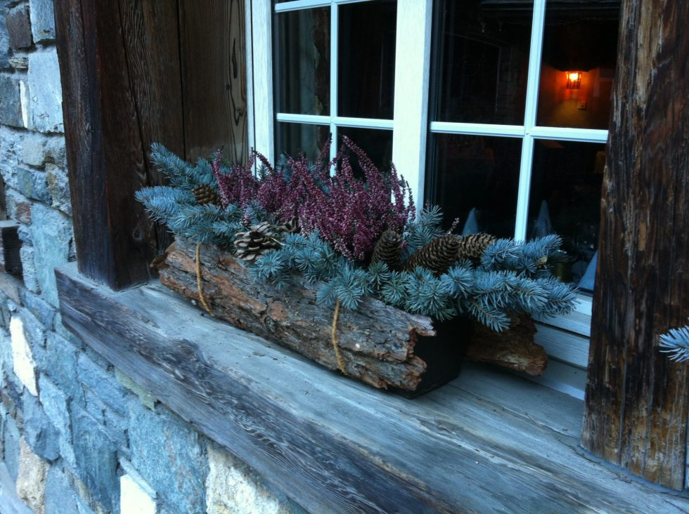 Window boxes with bark and evergreen makes a natural Christmas decor idea