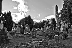 Round tower and grave slabs at Glendalough Monastic Site