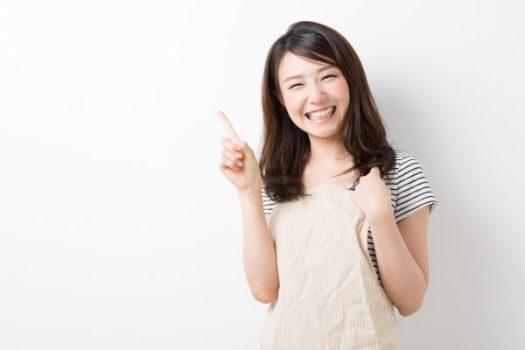 笑顔で人差し指を立てる女性のイメージ画像
