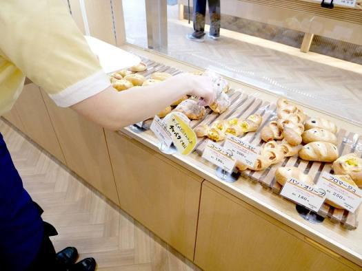 「豊島屋 扉店」のパンを陳列中のスタッフ
