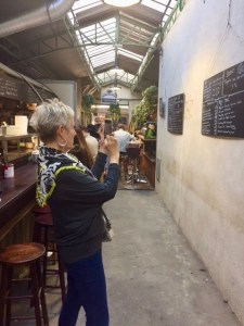 Me holding my iPhone taking a picture of a menu in the Le Marais Market