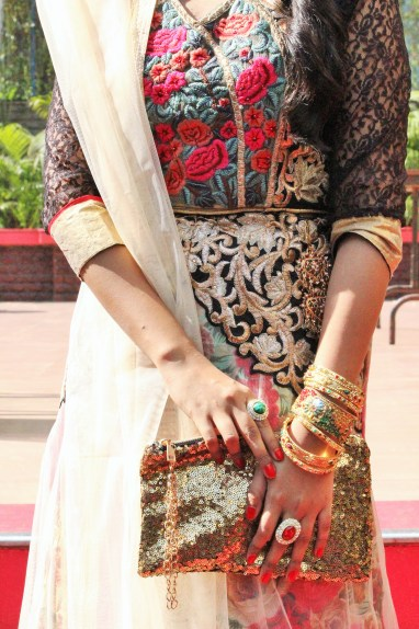 Lehenga details with bangles, golden purse, rings.