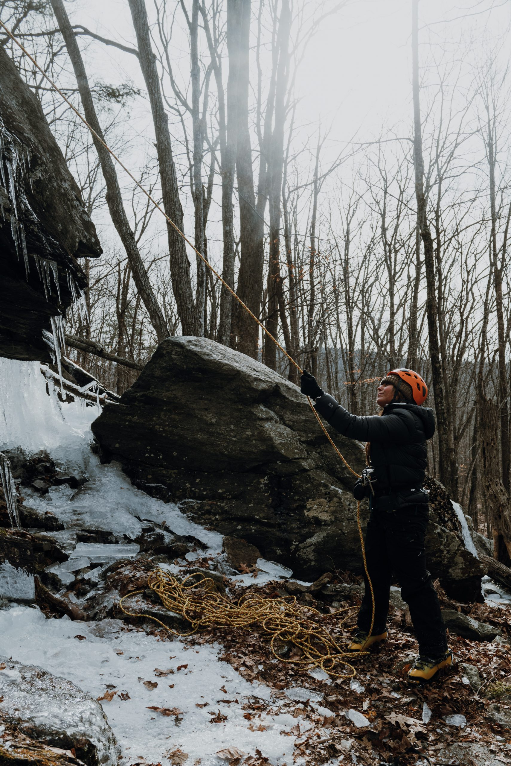 Girl belaying climber Ice Climbing in Camden Maine