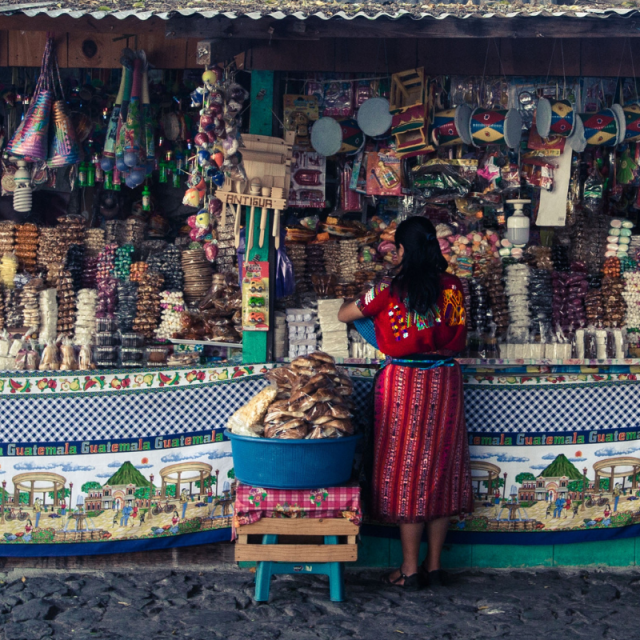 Woman in Guatemala standing in front of a candy stand