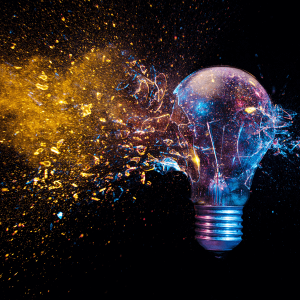 A photo of a lightbulb against a black background. Gold dust and multi-colored glitter is exploding from the light bulb.