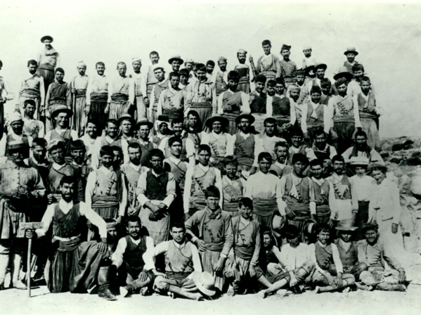 Sepia toned photos shows a large group of men dressed in local garb and Harriet Boyd Hawes. Everyone in the photo was involved in the dig.