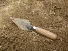 Image shows a flat trowel with a wooden handle sitting in the dirt.