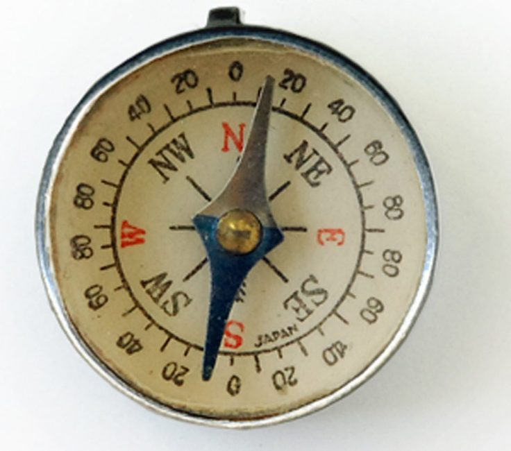 Image of a mechanical compass with the arrow point just slightly east of north.