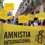 Brazilians carry an Amnesty Internationl banner through the streets.