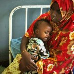 Somalia mother comforts ill child.