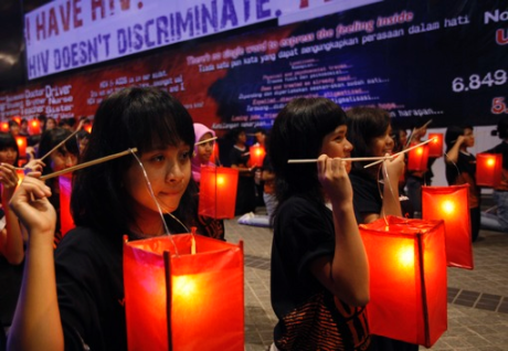 Students carry lanterns during a World AIDS Day event