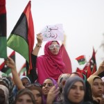 Libyan women in a rally raving revolutionary flags and showing V for victory