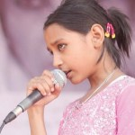 Young girl speaks at microphone