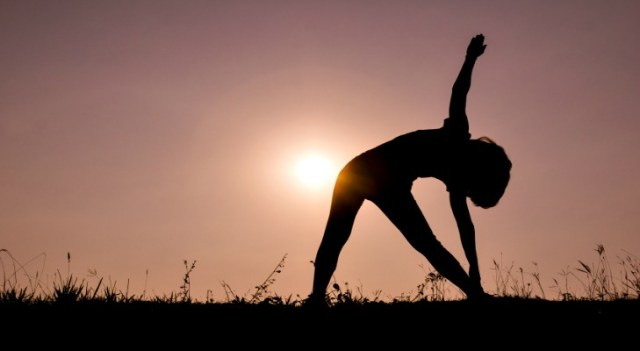 Triangle pose yoga with young woman silhouette on sunset sky.