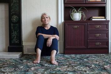 image of older woman sitting on floor looking sad