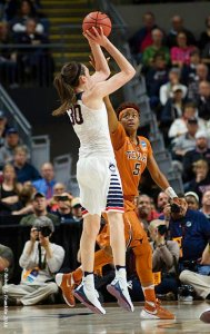 Breanna Stewart (11) of UConn shoots and makes a basket as Texas's Jordan Horsey (5) commits a foul. Photo by Robert L. Franklin.