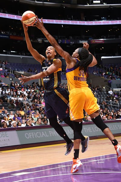 Tamika Catchings drives to the basket against Nneka Ogwumike. Photo by Andrew D. Bernstein/NBAE via Getty Images.