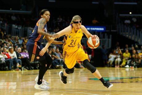 Sydney Wiese storms by Courtney Williams. Photo by Maria Noble/WomensHoopsWorld.