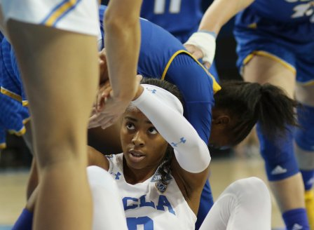 Jordin Canada is helped to her feet after a ball scramble. Photo by Maria Noble/WomensHoopsWorld.