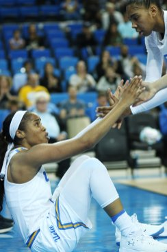 Jordin Canada is helped to her feet after a foul. Photo by Maria Noble/WomensHoopsWorld.