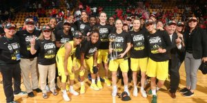 The 2018 WNBA Champion Seattle Storm pose with the trophy. Photo courtesy of Seattle Storm.