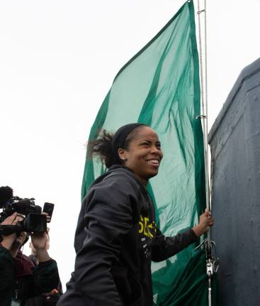 Jordan Canada braves the wind to help hoist the Storm flag. Neil Enns/Storm Photos.