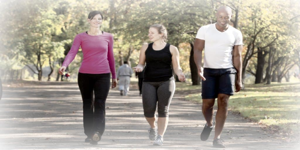 Three people walking in a park, getting some exercise